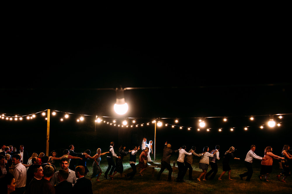 couple kissing under the festoon lights while guests gatecrash doing the conga