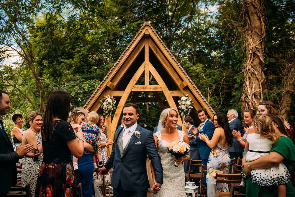 couple leave the outdoor ceremony at Rivervale barn