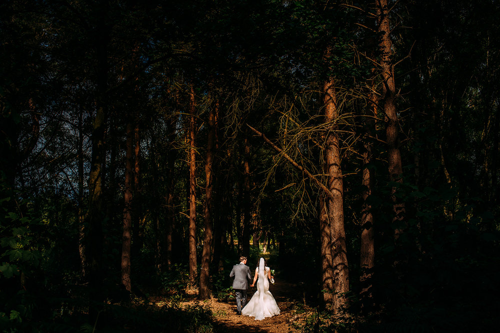 couple walk into the woods at Nunsmere hall