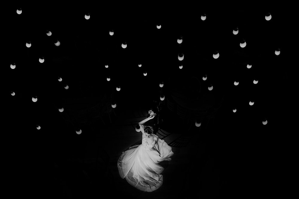 Black & white photo of the bride during the first dance, taken through festoon lights