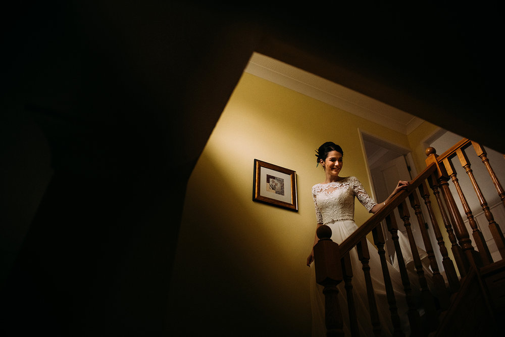 bride coming down the stairs at her home