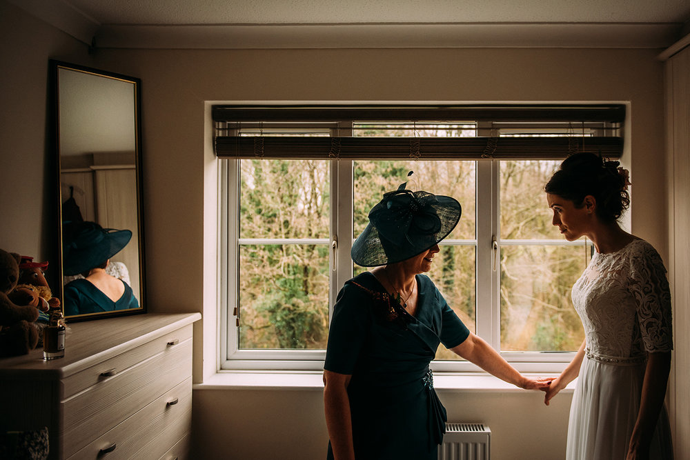 Bride's mother touches her hand for reassurance