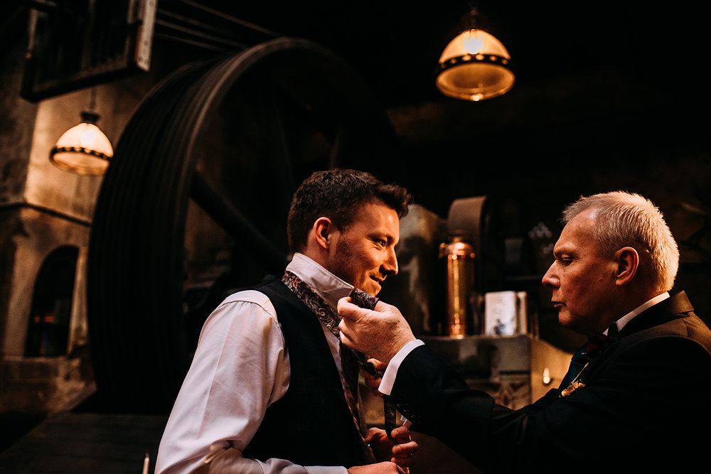 Groom having his tie done by his father