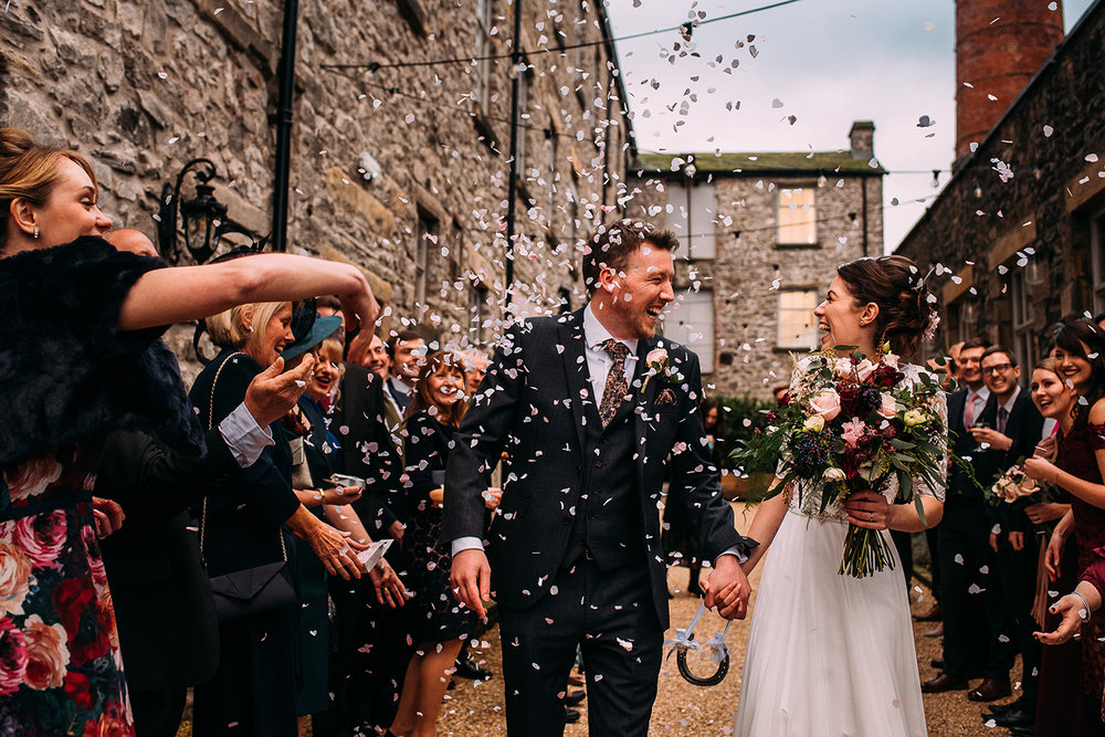 bride and groom laughing and walking through confetti