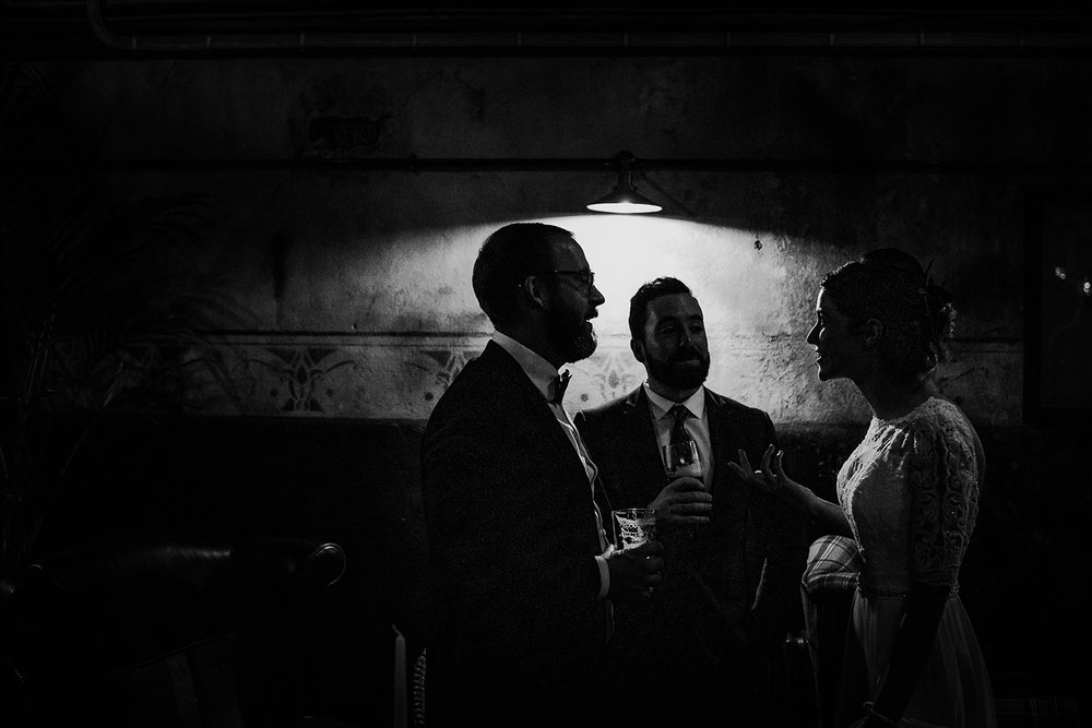 bw silhouette of guests under a lamp