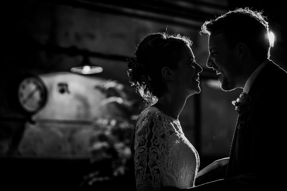 black and white back lit photo of the bride and groom laughing