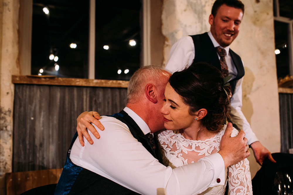 bride hugging her father after his speech