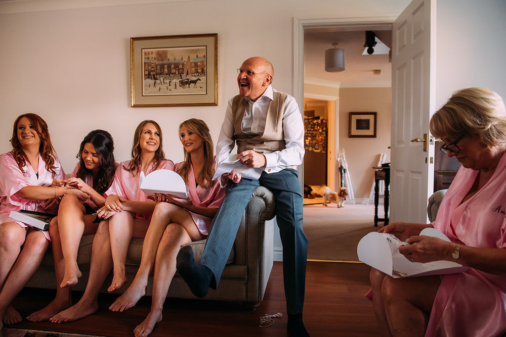 bridesmaids and dad on the couch laughing with the dog in the background
