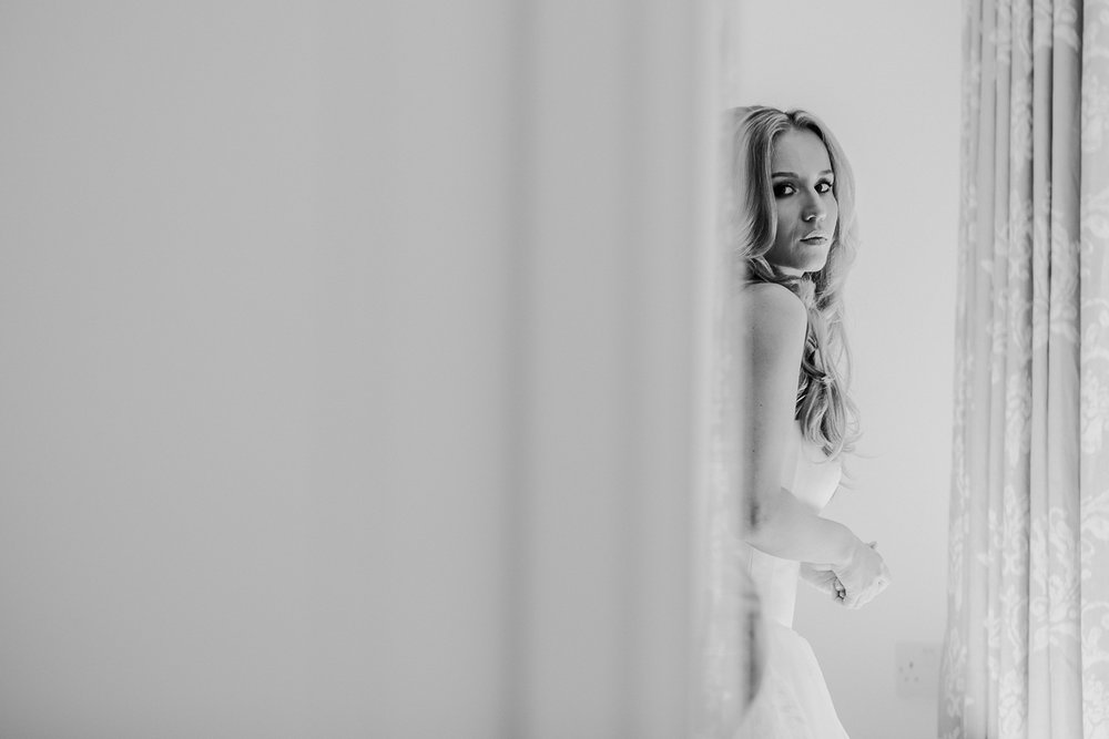 bw photo of bride looking in the mirror