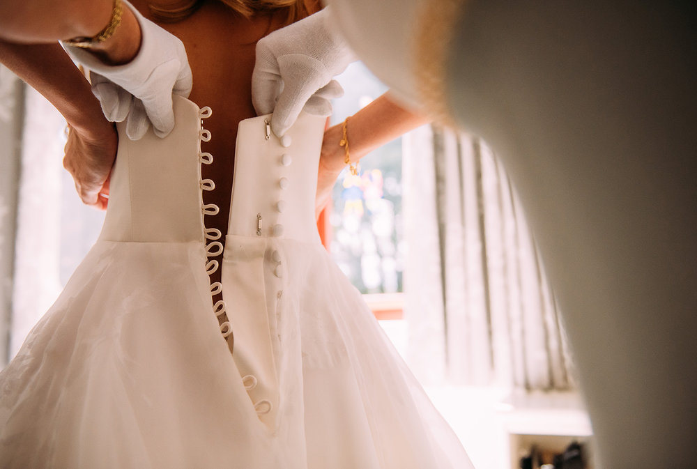 mother fastening the brides dress