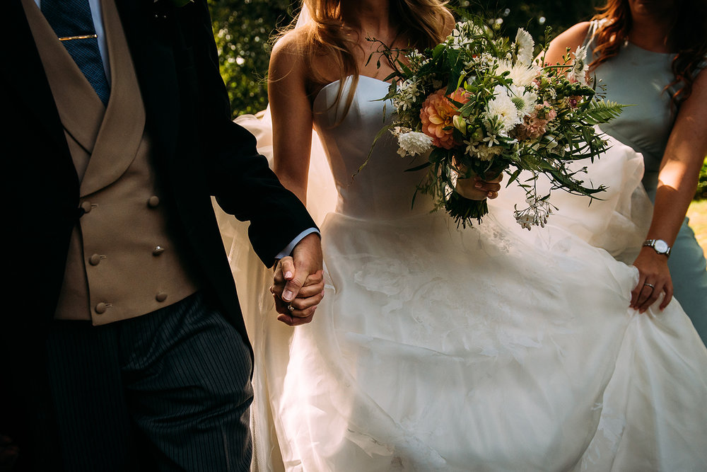 bride and her father holding hands