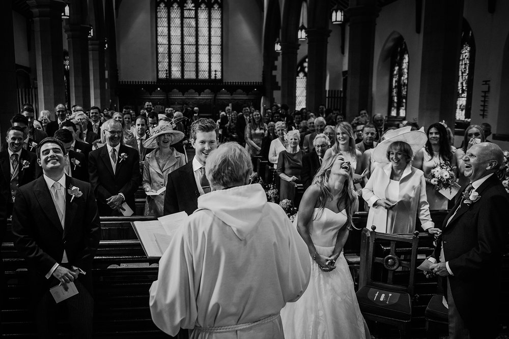 BW photo of every one in church laughing