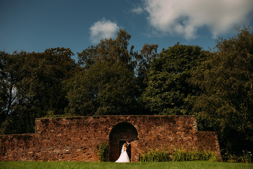 bride and groom kissing in front of a huge wall
