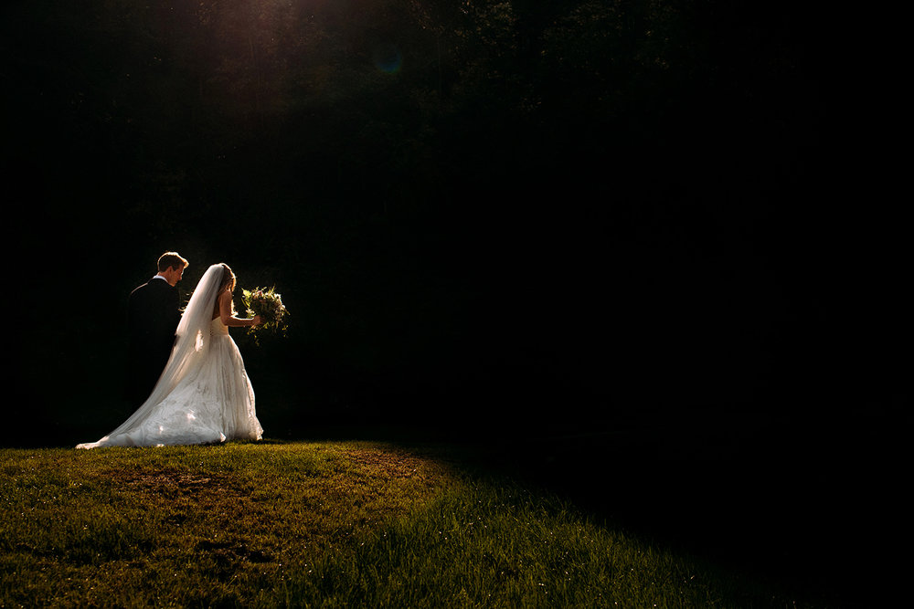 bride and groom walking through nice light into a darker area