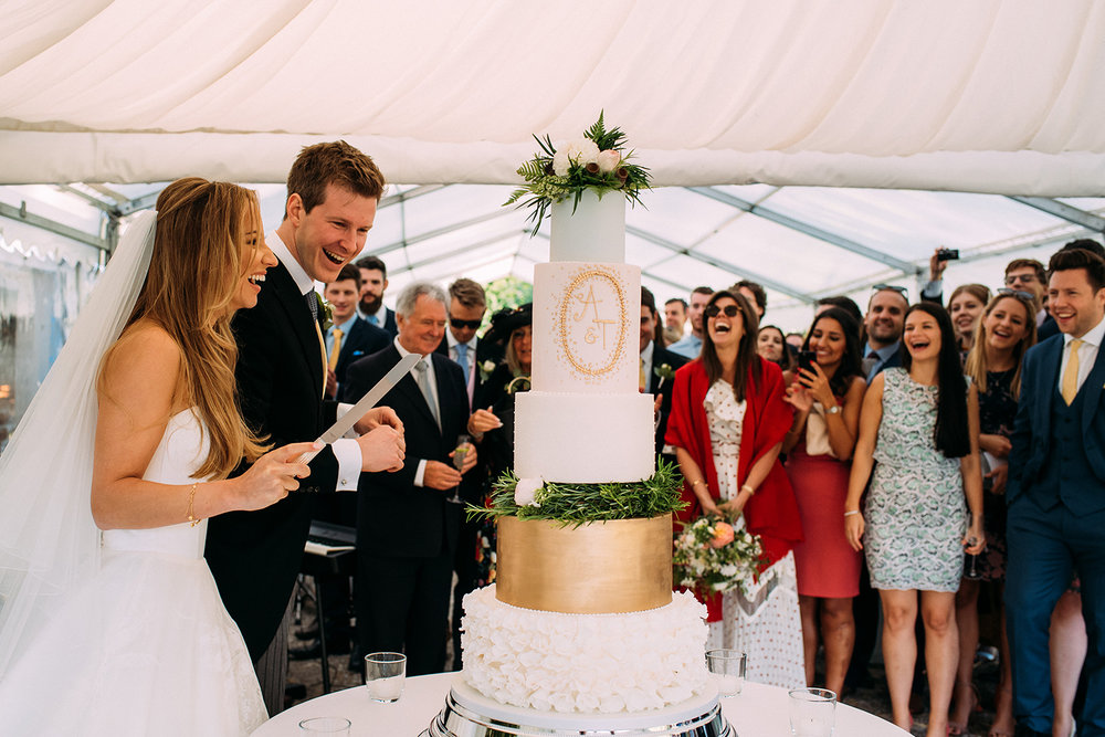 guest look on and laugh as they cut the cake