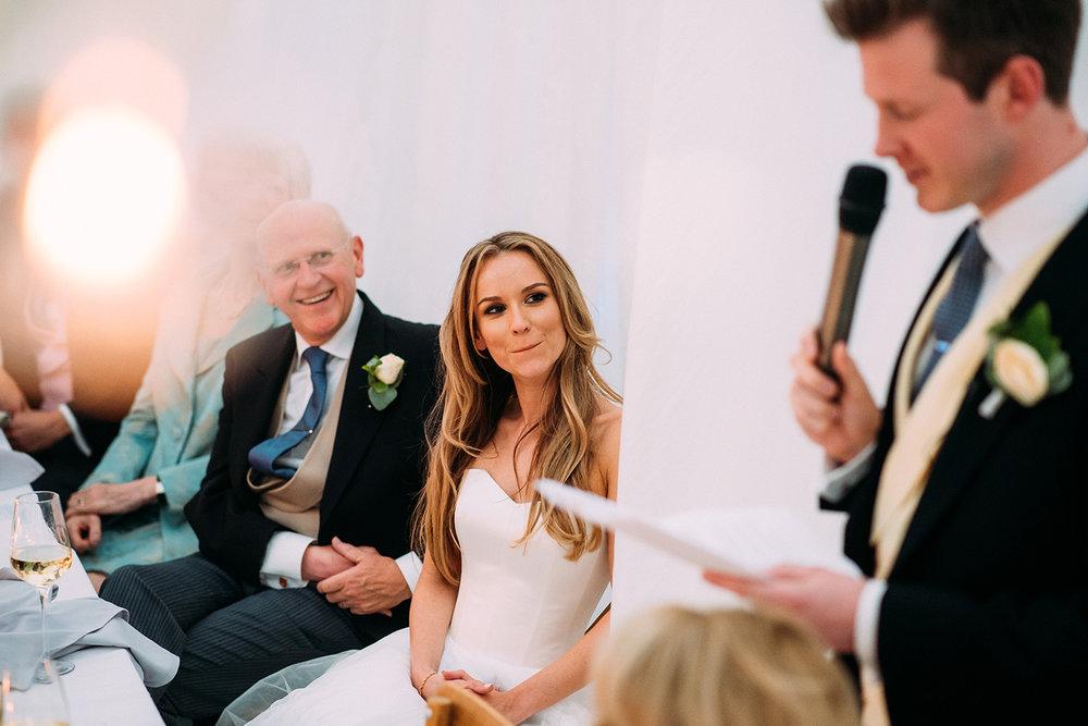 bride looking at groom during his speech
