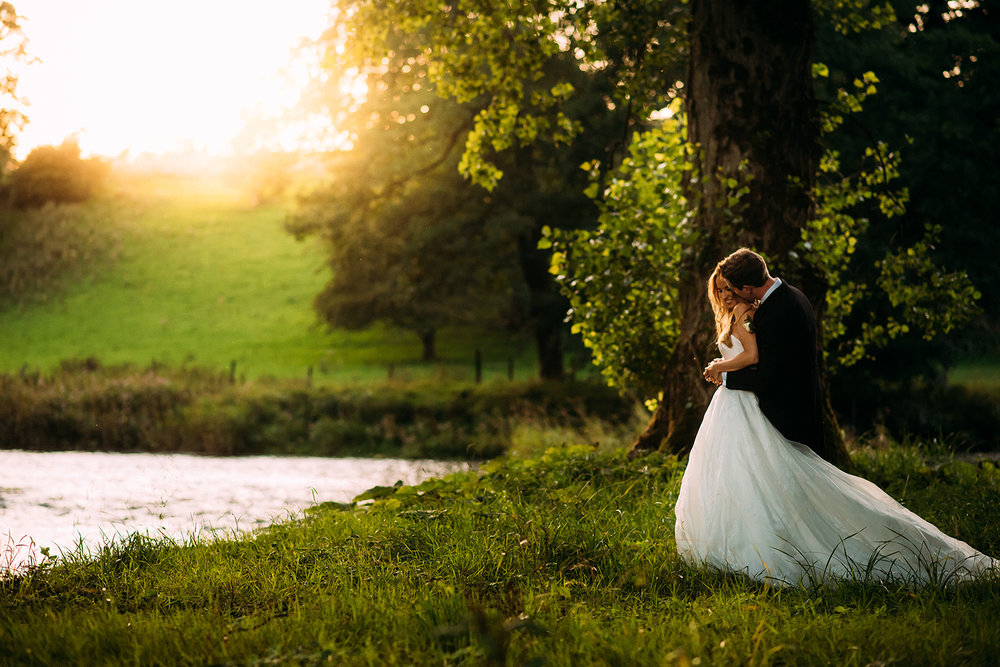 bride and groom cuddle byt the river at sunset