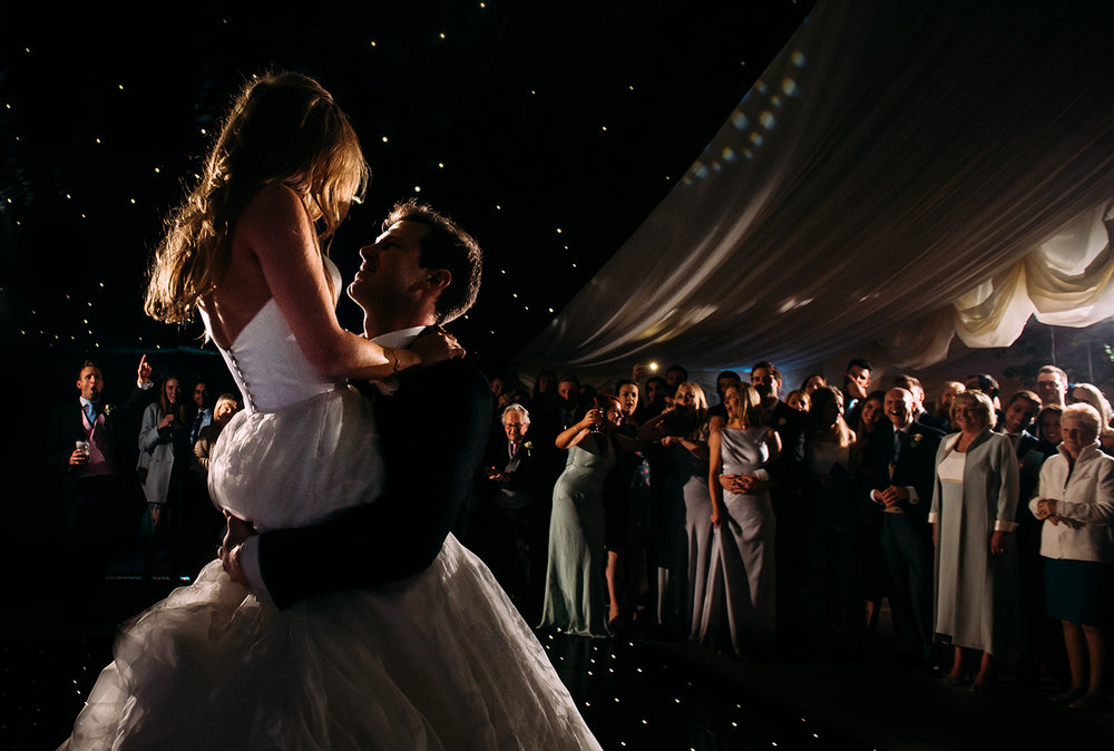 groom lifts and spins his wife during the first dance