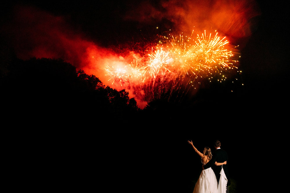 bride and groom. Bride lifts her arm in the air as fireworks go off