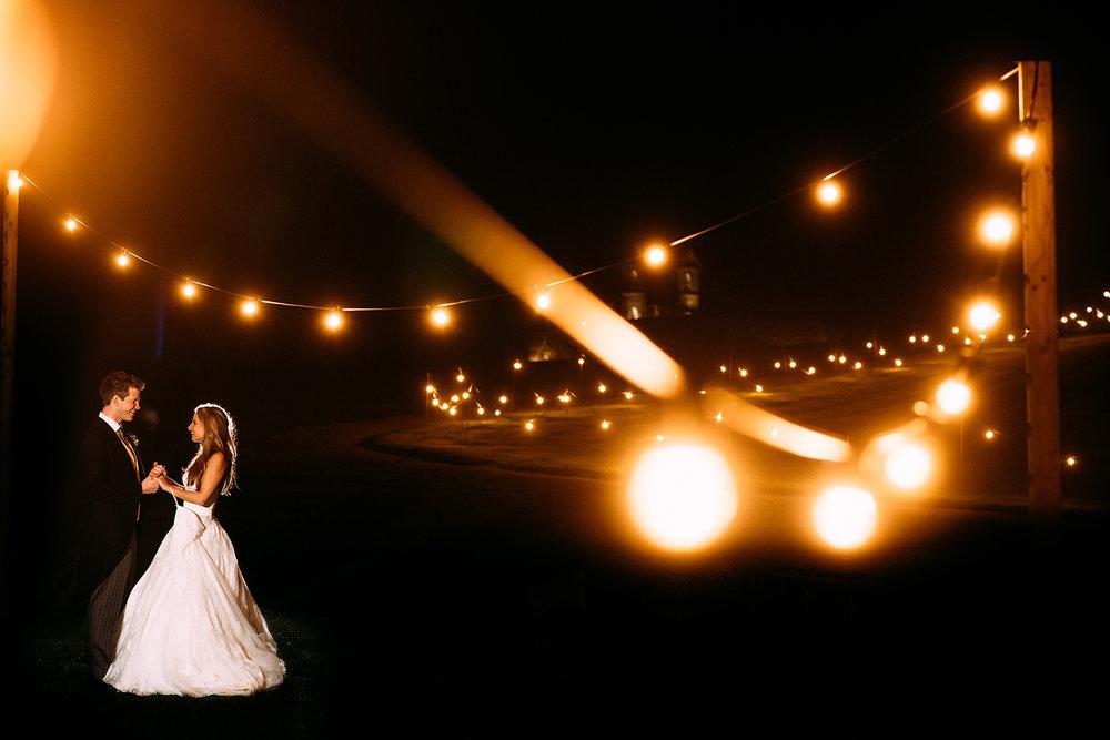 off camera flash night time portrait of bride and groom taken through festoon lights