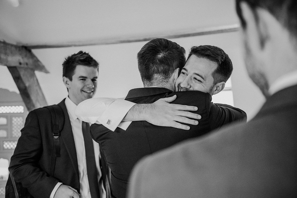 BW photo of the groom hugging his friends