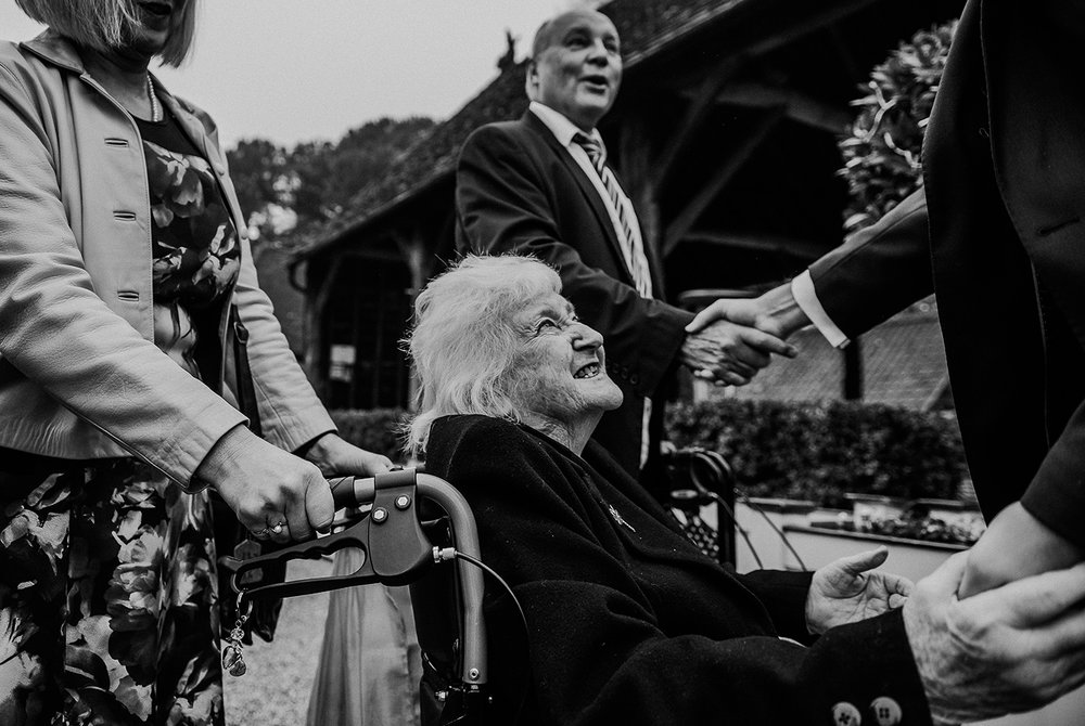 elderly relative greeting the groom while he also shakes someone else's hand