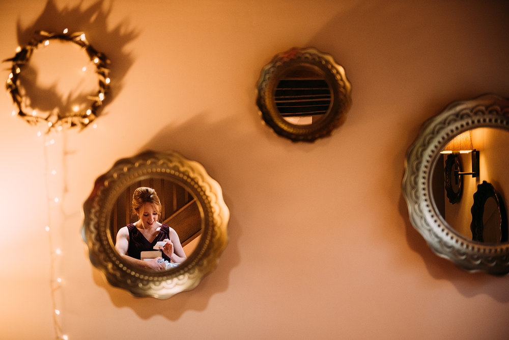 reflection of chief bridesmaid fastening bracelet on a wall full of mirrors