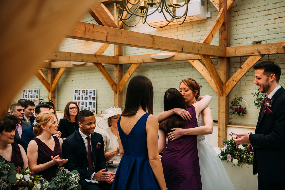 the bride kissing the friends after the reading
