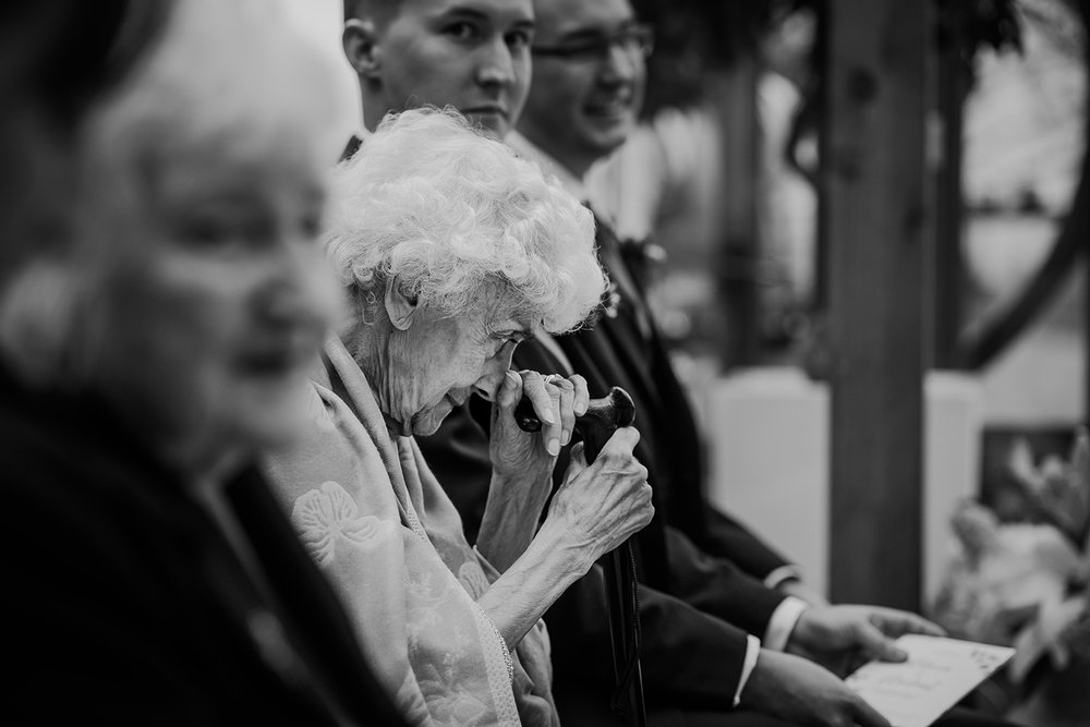 BW photo of gran resting her head on her walking stick