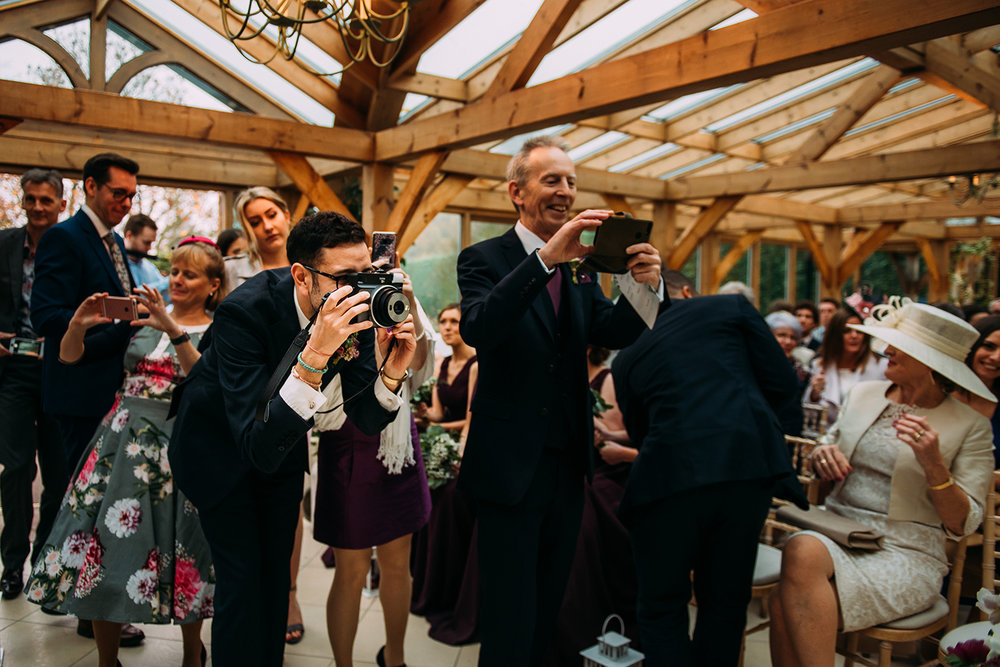 guests taking photo's of the couple as they sign the register