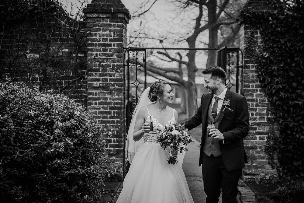 BW photo of the couple walking through the gardens