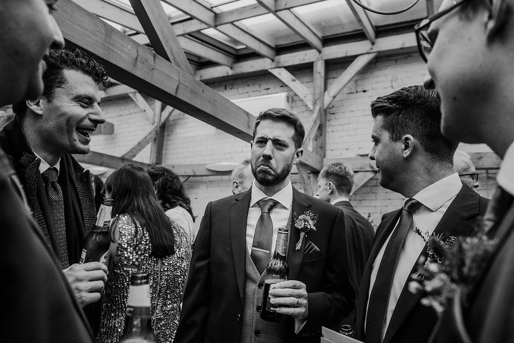 BW photo of the groom having a laugh with his friends