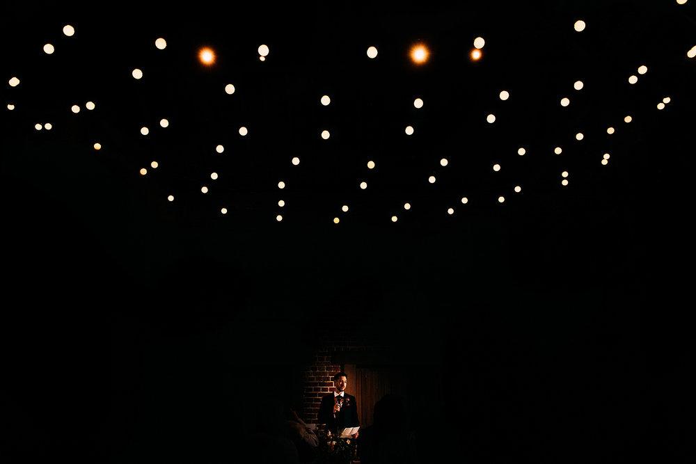groom lit up under lights during his speech