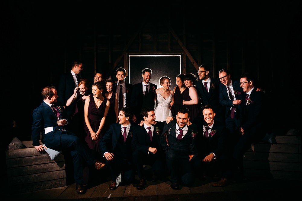 big group photo of the bridal party in the barn