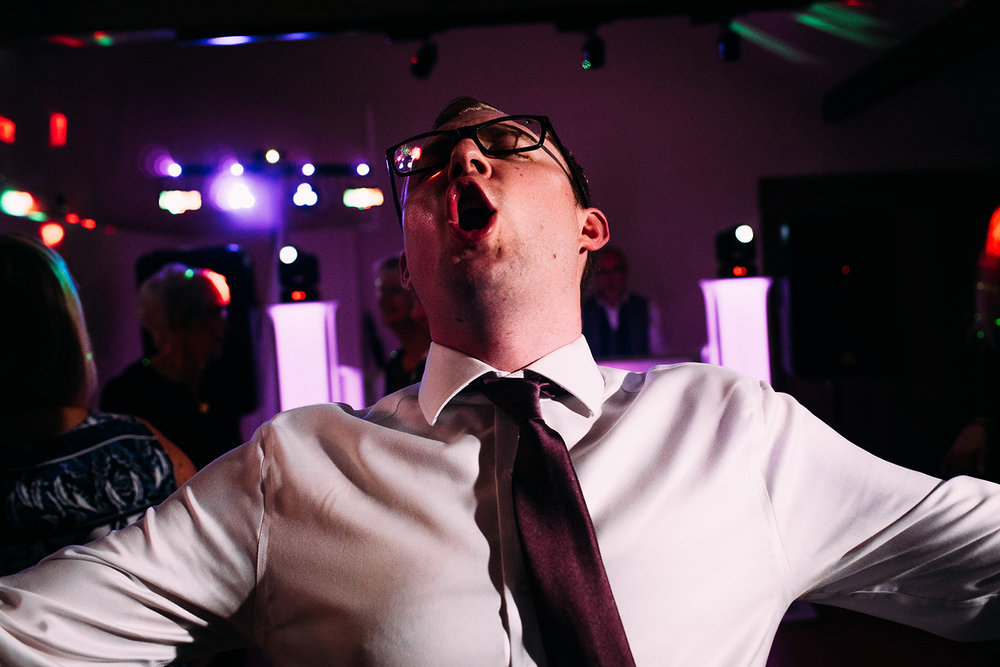 close up of a man shouting on the dance floor