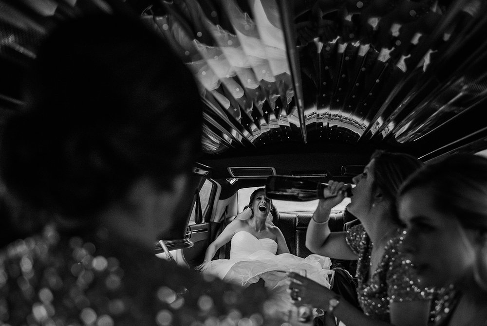 bw photo of bride laughing at her sister in the limo
