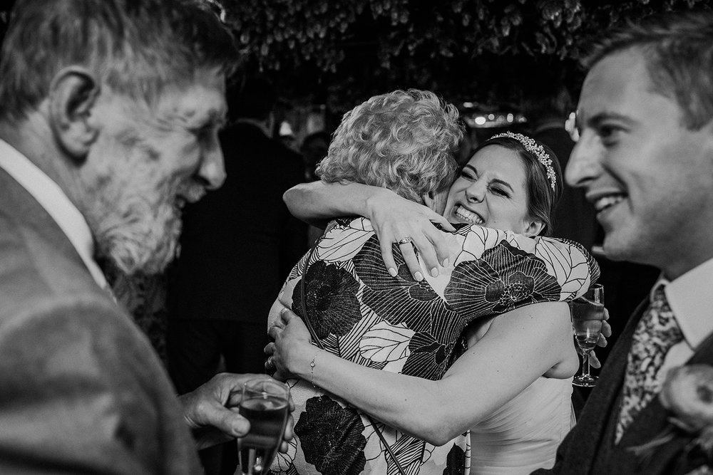 bw photo of the bride squeezing a guest framed by the groom and another guest laughing at each other