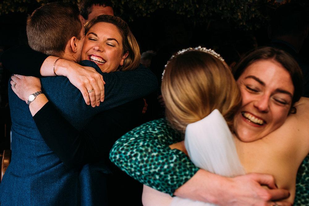 bride hugging guest mirrored by groom hugging guest