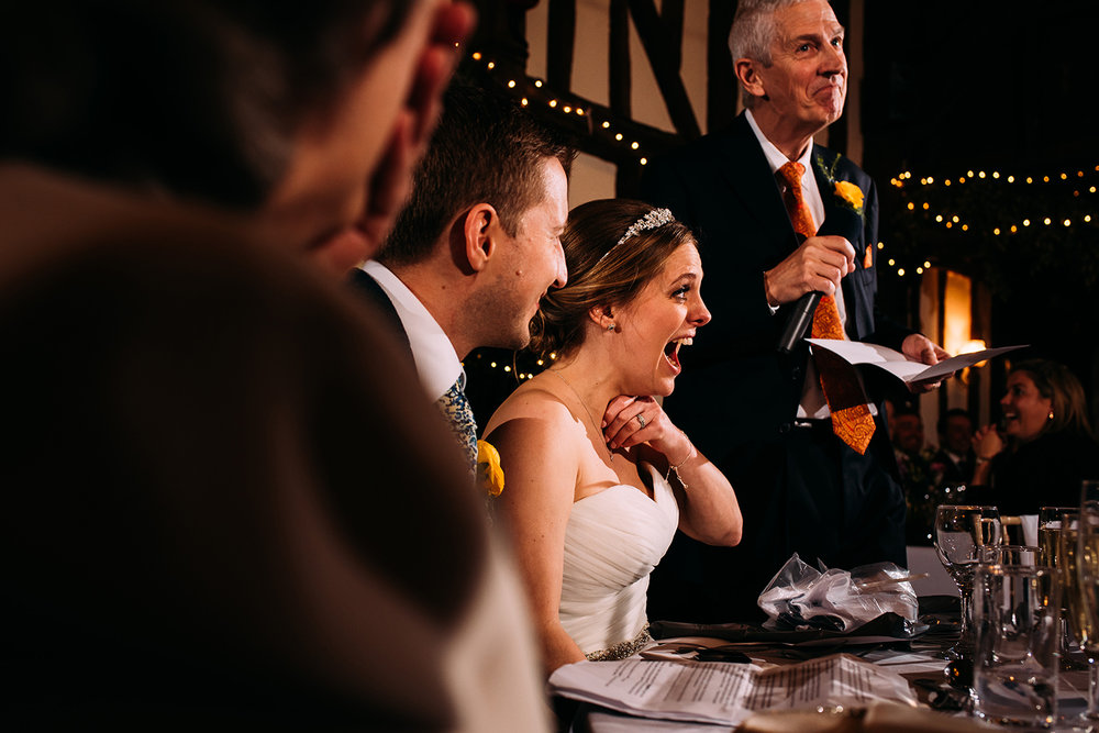 bride laughing as her father gives his speech