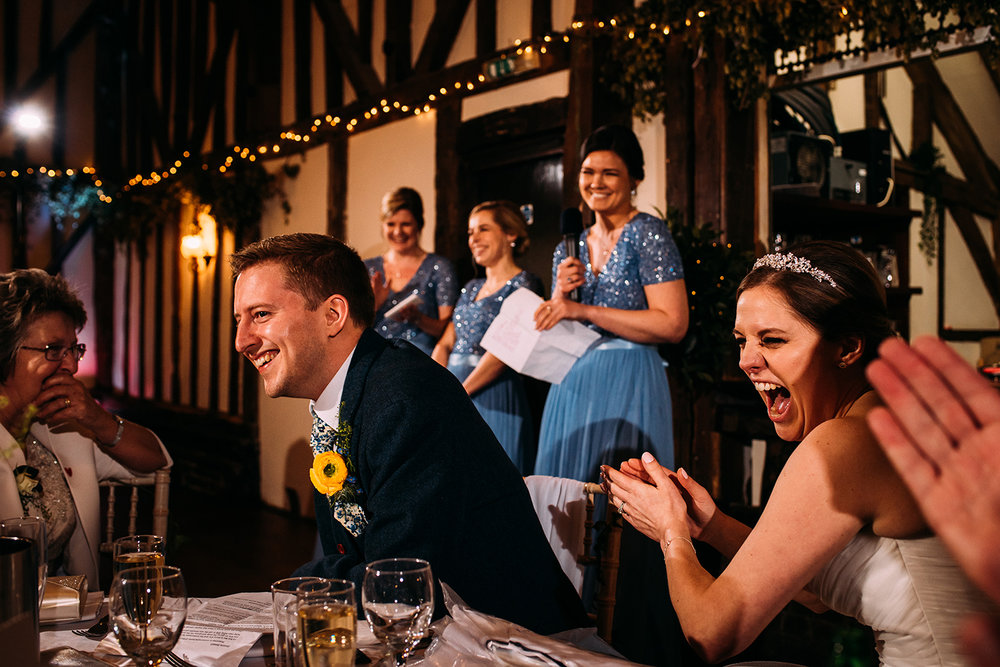 bride, groom, and bridesmaids laughing