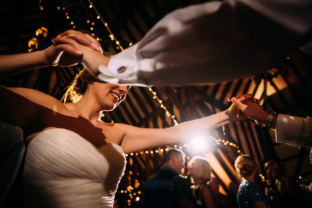 low angle dancing shot of the bride and groom holding hands
