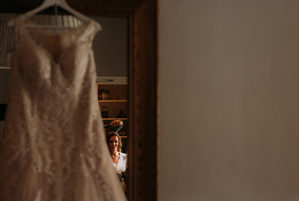 brides refection in the mirror behind the hanging wedding dress