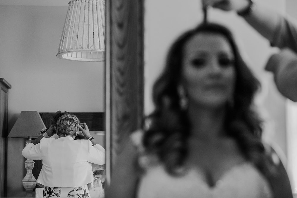 bw split composition. Bride having hair done to the right and mum checking reflection to the left