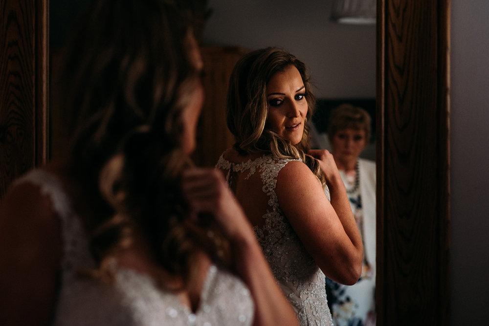 bride checks reflection in mirror