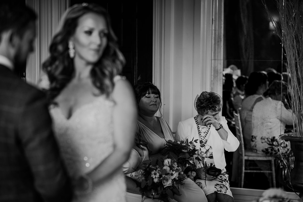 bw photo bride and groom to the left but focus is on the brides mother wiping her tears to the right