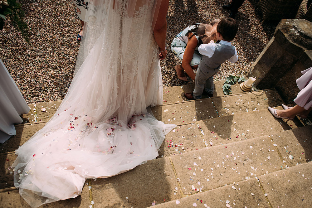 back of the brides dress on the steps covered in confetti and a boy on the steps to the right