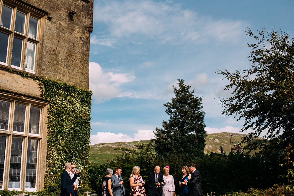 guests having drinks outside falcon manor with countryside views