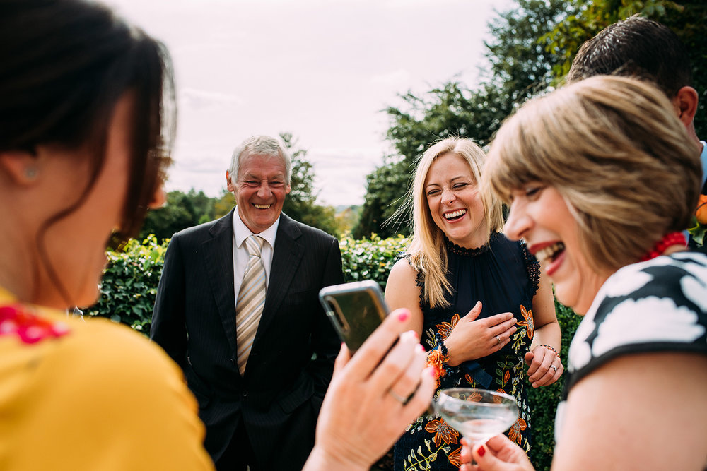 guests laughing at something on guests phone