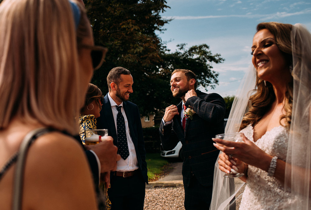 layered shot of bride and groom laughing with friends