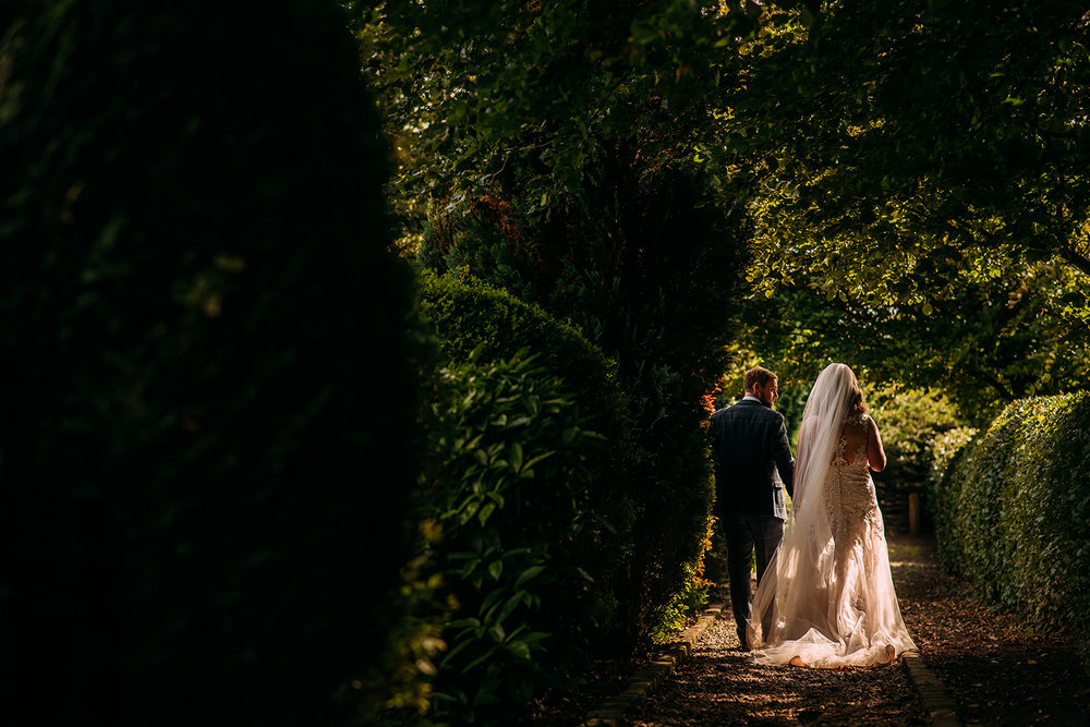 bride and groom walking through the gardens
